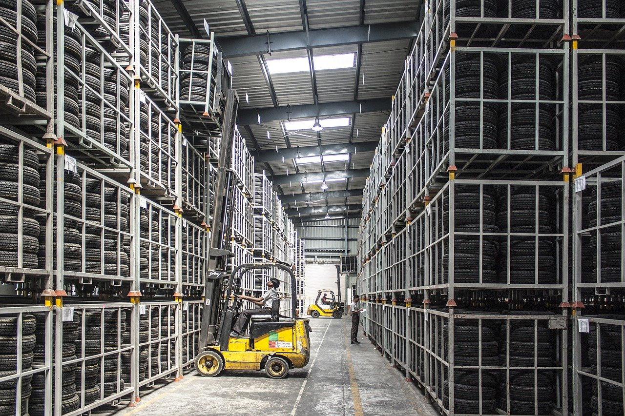 A forklift driver pulls inventory off warehouse rack