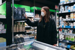 A lady wearing mask is choosing a product from the shelve