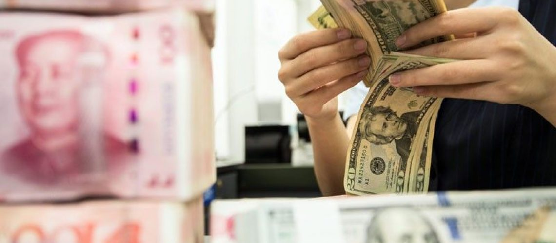 A Chinese bank employee counts 100-yuan notes and US dollar bills at a bank counter in Nantong in China's eastern Jiangsu province. The United States formally retracted its accusation that China manipulates its currency to gain unfair trade advantages, according to a media report. AFP.