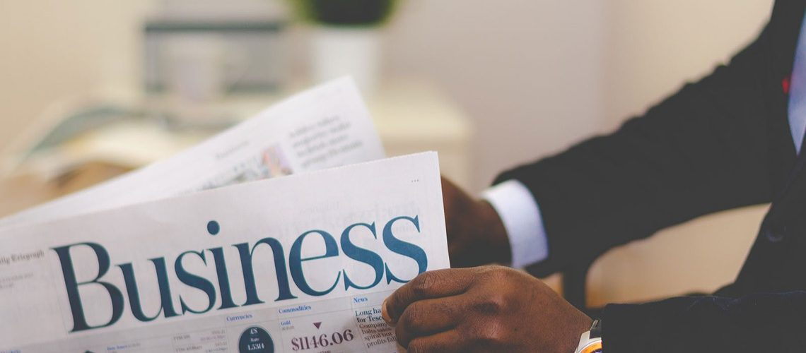 A businessman is reading a newspaper
